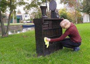 Afstoffen van het monument voor Carry van Bruggen in Zaandam